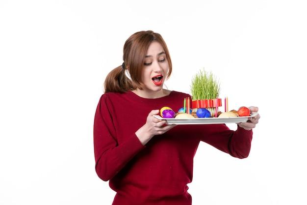 흰색 배경에 semeni와 novruz 과자를 들고 혼카를 들고 있는 젊은 여성의 전면 보기 민족 공연자 민족성 휴일 봄 색상