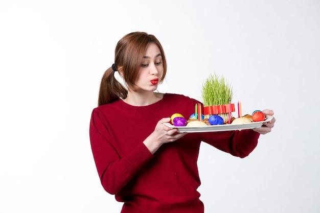 Вид спереди молодой женщины, держащей хонка с семени и новруз конфетами на белом фоне этнический исполнитель этничность праздники концепция весенние цвета