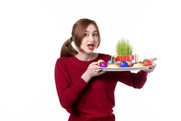 Вид спереди молодой женщины, держащей хонка с семени и новруз конфетами на белом фоне этнический исполнитель концепция праздника весенние цвета