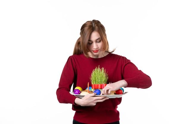 Вид спереди молодой женщины, держащей хонка с семени и новруз конфетами на белом фоне праздничные цвета концепция этнической принадлежности этнический исполнитель