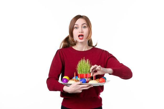 흰색 바탕에 semeni 및 novruz 과자를 들고 혼카를 들고 있는 젊은 여성의 전면 보기 휴일 색상 민족성 개념 민족 봄 공연자