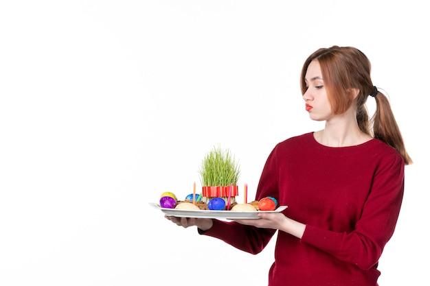 흰색 바탕에 semeni와 novruz 과자가 있는 혼카를 들고 있는 젊은 여성의 전면 보기 휴일 민족 색상 개념 민족 봄