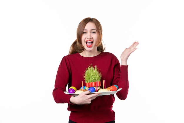 흰색 바탕에 semeni 및 novruz 과자를 들고 혼카를 들고 있는 젊은 여성의 전면 보기 휴일 민족 개념 민족 공연자 색상