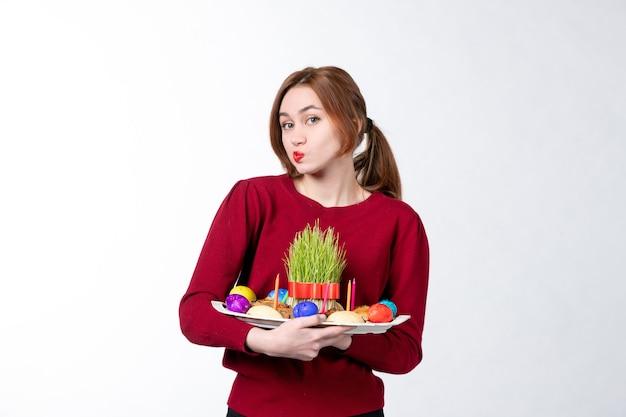 흰색 배경 휴일 민족 개념 민족 봄 색상에 semeni 및 novruz 과자와 함께 혼카를 들고 젊은 여성의 전면보기