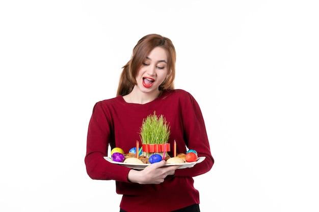 흰색 바탕에 semeni와 novruz 과자를 들고 혼카를 들고 있는 젊은 여성의 전면 보기 휴일 민족 개념 민족 봄 공연 색상