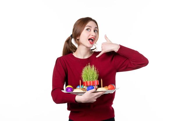 흰색 바탕에 semeni 및 novruz 과자를 들고 혼카를 들고 있는 젊은 여성의 전면 보기 휴일 민족 민족 봄 공연자 색상 개념