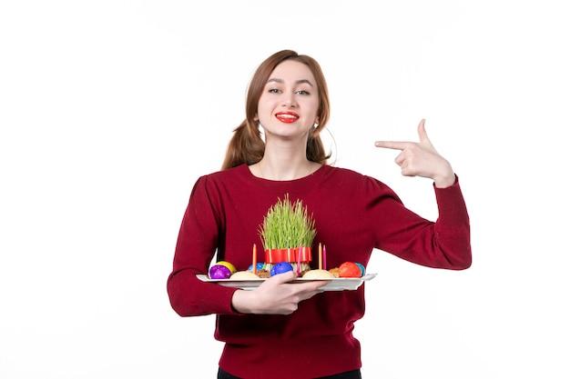 흰색 바탕에 semeni와 novruz 과자가 있는 혼카를 들고 있는 젊은 여성의 전면 보기 휴일 민족 민족 봄 공연자 색상