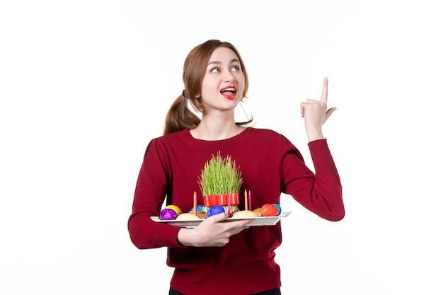 흰색 배경에 세메니와 노브루즈 과자를 들고 혼카를 들고 있는 젊은 여성의 전면 보기 휴일 민족 민족 봄 공연자 개념