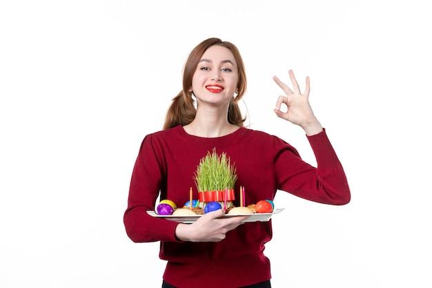 흰색 배경에 semeni와 novruz 과자를 들고 혼카를 들고 있는 젊은 여성의 전면 보기 휴일 민족 민족 봄 공연 색상 개념