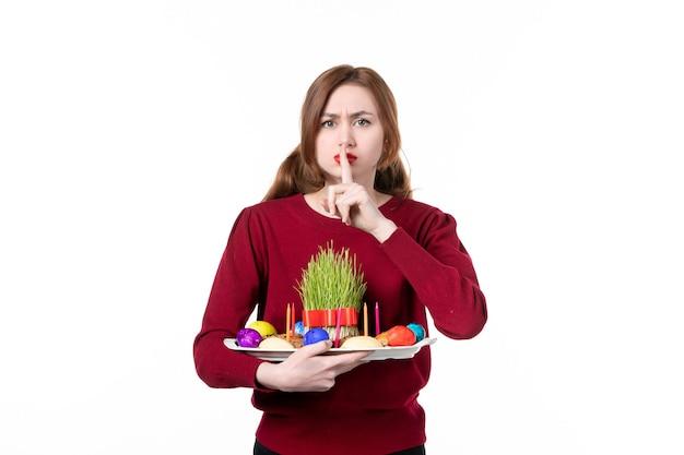 흰색 배경에 semeni와 novruz 과자를 들고 혼카를 들고 있는 젊은 여성의 전면 보기 휴일 민족 수행자 색상 개념 민족 봄
