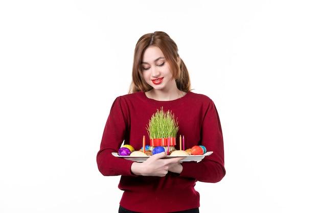 흰색 배경에 세메니와 노브루즈 과자를 곁들인 혼카를 들고 있는 젊은 여성의 전면 보기 휴일 민족 수행자 색상 개념 봄