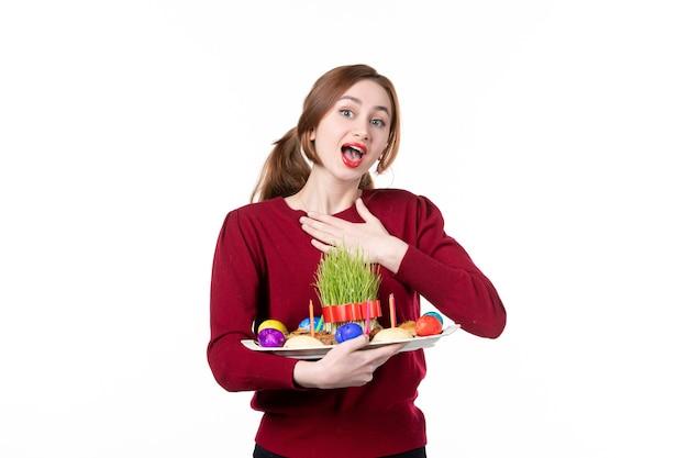 흰색 배경에 semeni 및 novruz 과자를 들고 혼카를 들고 있는 젊은 여성의 전면 보기 휴일 민족 수행자 색상 민족 봄