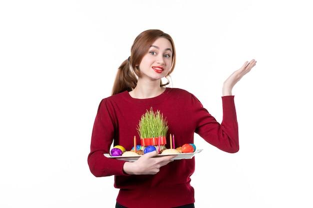 흰색 배경에 semeni 및 novruz 과자를 들고 혼카를 들고 있는 젊은 여성의 전면 보기 휴일 민족 봄 색상 개념 민족