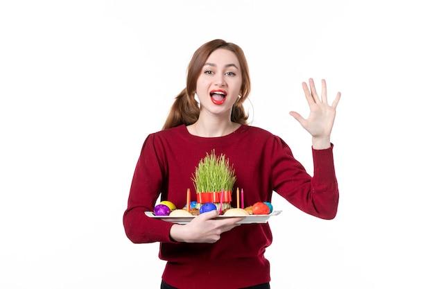 白い背景の上のsemeniとnovruzのお菓子とhoncaを保持している若い女性の正面図休日民族春パフォーマー色概念民族