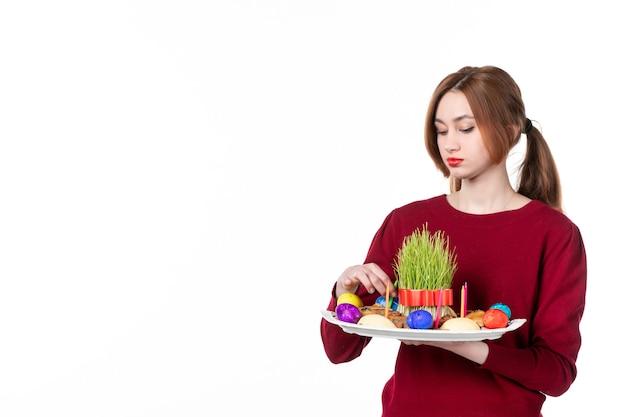Вид спереди молодой женщины, держащей хонка с семени и новруз конфетами на белом фоне исполнитель этническая принадлежность цвета концепция этническая весна