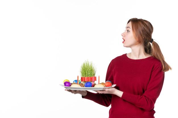 白い背景の上のsemeniとnovruzのお菓子とhoncaを保持している若い女性の正面図パフォーマー休日民族色コンセプト民族春