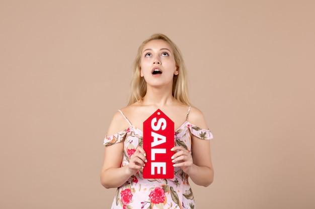 茶色の壁に赤い販売ボードを保持している若い女性の正面図