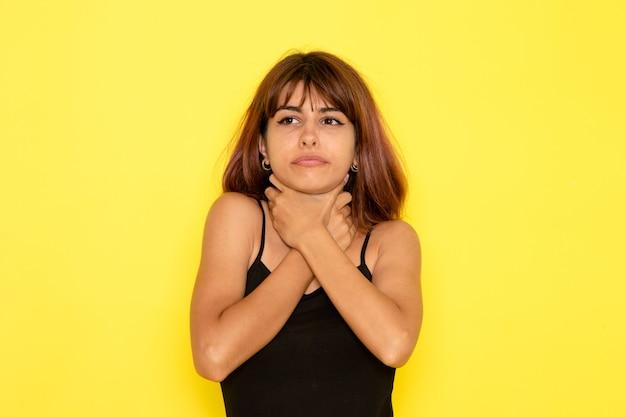黒のシャツと黄色の壁に身をかがめる灰色のジーンズの若い女性の正面図