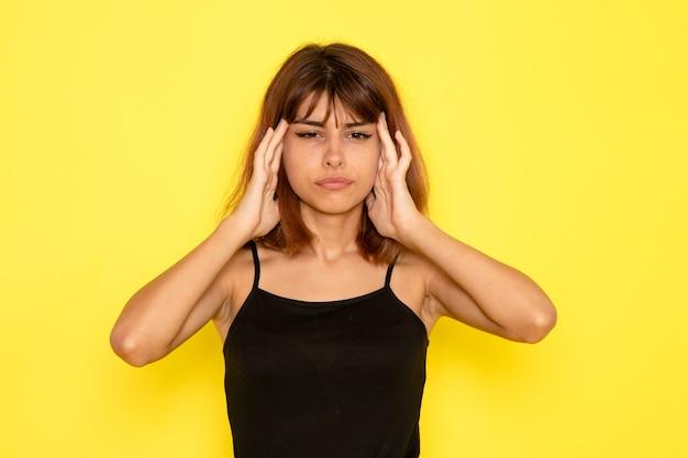 노란색 벽에 두통을 가진 검은 셔츠와 회색 청바지에 젊은 여성의 전면보기