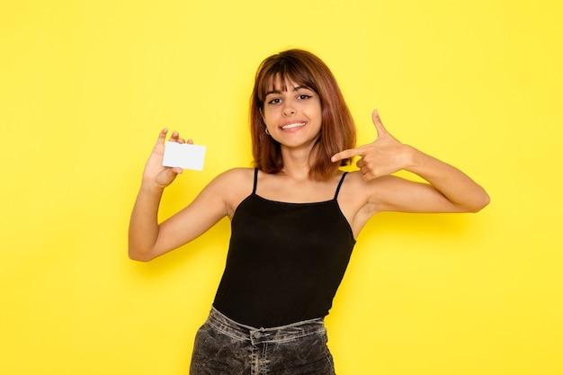 노란색 벽에 플라스틱 카드를 들고 검은 셔츠와 회색 청바지에 젊은 여성의 전면보기