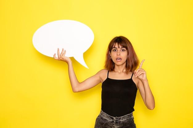 밝은 노란색 벽에 큰 흰색 기호를 들고 검은 셔츠와 회색 청바지에 젊은 여성의 전면보기