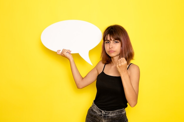 노란색 벽에 큰 흰색 기호를 들고 검은 셔츠와 회색 청바지에 젊은 여성의 전면보기