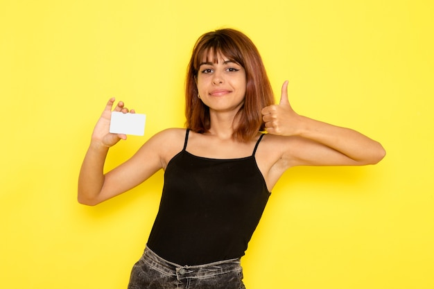 검은 셔츠와 노란색 벽에 카드를 들고 회색 청바지에 젊은 여성의 전면보기