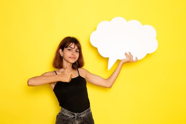 노란색 벽에 거대한 흰색 기호를 들고 검은 셔츠와 회색 청바지에 젊은 여성의 전면보기