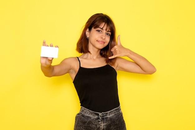 노란색 벽에 흰색 카드를 들고 검은 셔츠와 회색 청바지에 젊은 여성의 전면보기