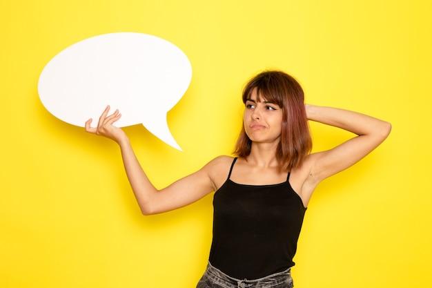 노란색 벽에 흰색 기호를 들고 검은 셔츠와 회색 청바지에 젊은 여성의 전면보기