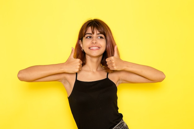 검은 셔츠와 노란색 벽에 웃 고 회색 청바지에 젊은 여성의 전면보기