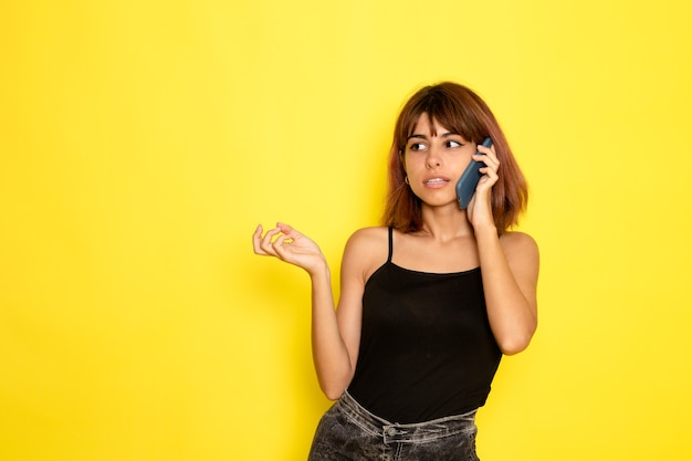 노란색 벽에 전화 통화 검은 셔츠와 회색 청바지에 젊은 여성의 전면보기
