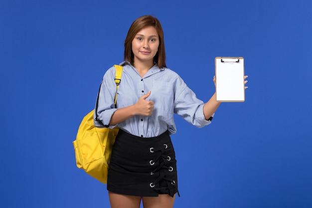 水色の壁にメモ帳を保持している黄色のバックパックを身に着けている青いシャツの黒いスカートの若い女性の正面図