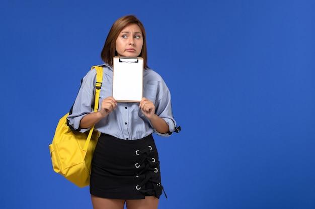 Вид спереди молодой женщины в синей рубашке с черной юбкой в желтом рюкзаке с блокнотом и мышлением на голубой стене