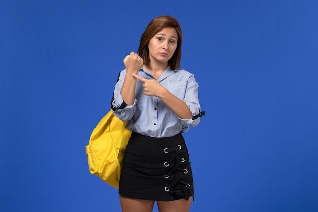 밝은 파란색 벽에 그녀의 손목에서 지적하는 노란색 배낭을 입고 파란색 셔츠 검은 치마에 젊은 여성의 전면보기
