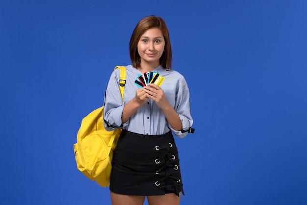 Вид спереди молодой женщины в синей рубашке в желтом рюкзаке, держащей карты на голубой стене
