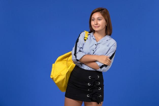 Вид спереди молодой женщины в синей рубашке, носить желтый рюкзак, позирует, улыбаясь на голубой стене