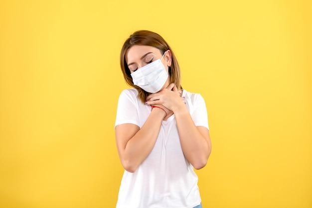 노란색 벽에 마스크에 젊은 여성의 전면보기