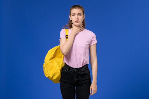 Вид спереди молодой женщины в розовой футболке с желтым рюкзаком, у которой болит горло на синей стене