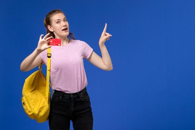 Вид спереди молодой женщины в розовой футболке в желтом рюкзаке, держащей пластиковую красную карточку на синей стене