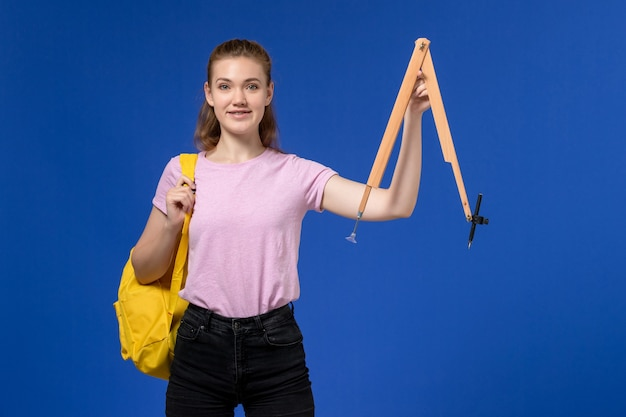 青い壁に木製の図を保持している黄色のバックパックを身に着けているピンクのtシャツの若い女性の正面図