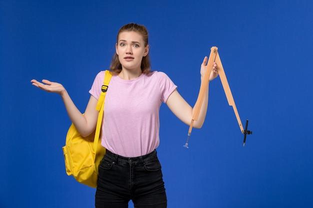 水色の壁に木製の図を保持している黄色のバックパックを身に着けているピンクのtシャツの若い女性の正面図