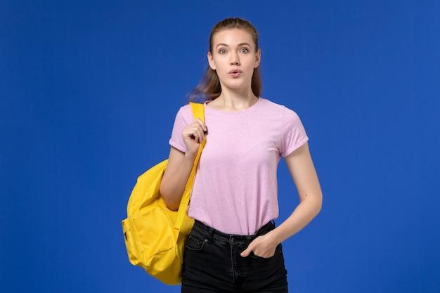 파란색 벽에 그냥 서있는 노란색 배낭을 입고 분홍색 티셔츠에 젊은 여성의 전면보기