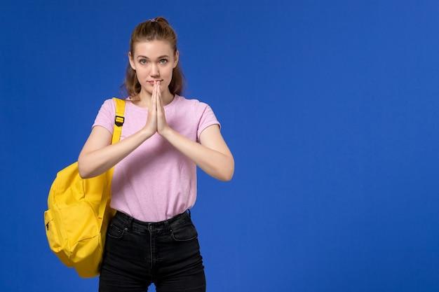 水色の壁に黄色のバックパックを身に着けているピンクのtシャツの若い女性の正面図