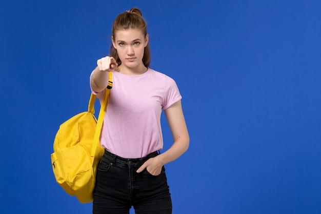 밝은 파란색 벽에 지적 노란색 배낭을 입고 분홍색 티셔츠에 젊은 여성의 전면보기