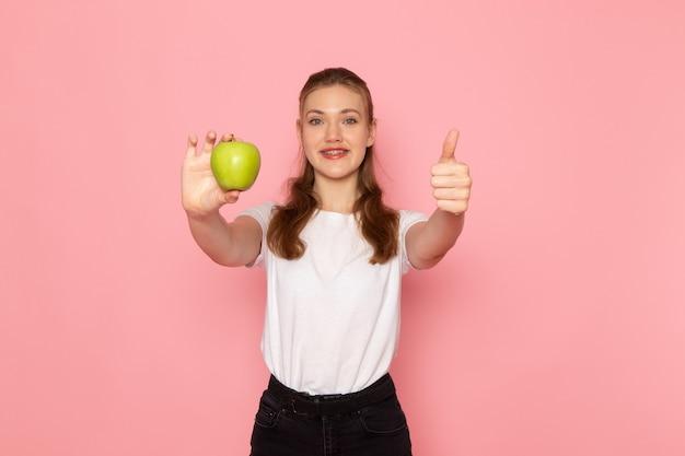 밝은 분홍색 벽에 신선한 녹색 사과를 들고 흰색 티셔츠에 젊은 여성의 전면보기