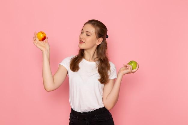 淡いピンクの壁に桃と新鮮な青リンゴを保持している白いtシャツの若い女性の正面図