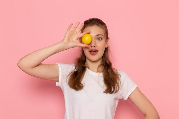 ピンクの壁に新鮮なレモンを保持している白いtシャツの若い女性の正面図
