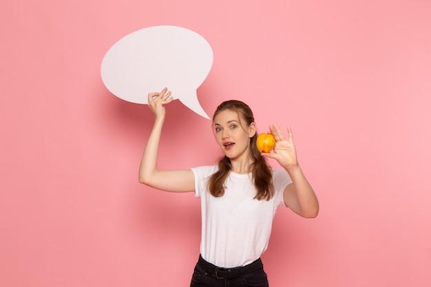 淡いピンクの壁に新鮮な桃を保持している白いtシャツの若い女性の正面図