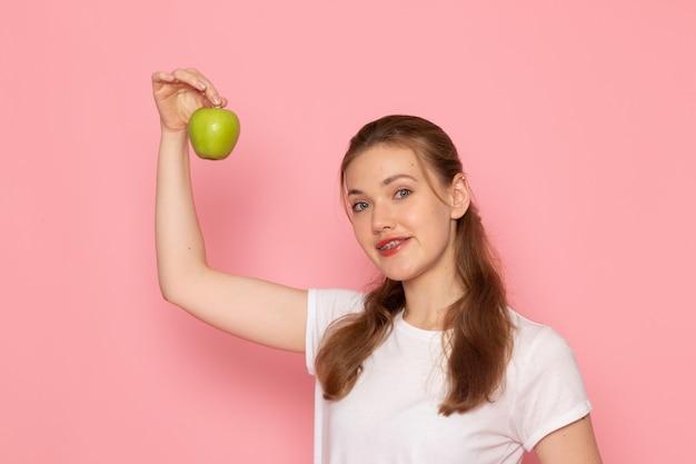 ピンクの壁に青リンゴを保持している白いtシャツの若い女性の正面図